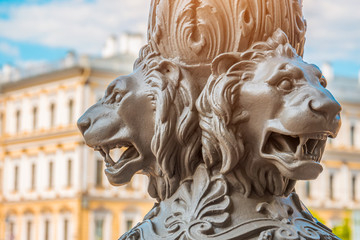 Antique architecture out of focus, in the foreground the sculpture of lions on a pillar, Saint-Petersburg, Russia.