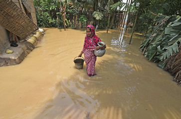 A woman carries drinking water after collecting it from a hand pump at a flood affected area in Hojai