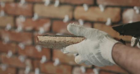 closeup worker applying concrete glue to brick tile