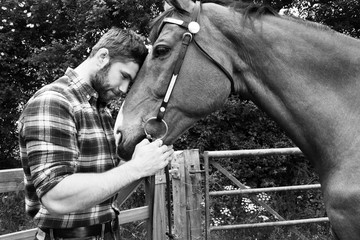 Handsome American cowboy, rider with checked, chequered shirt and jeans pets and loves his horse