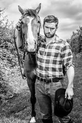 Handsome cowboy, horse rider on saddle, horseback adn boots