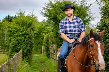 Handsome cowboy, horse rider on saddle, horseback and boots
