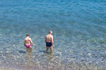 An elderly couple goes swimming in the sea