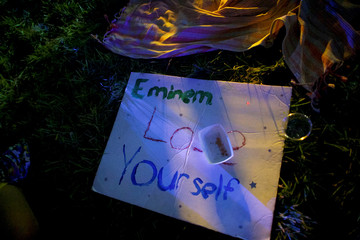 "A sign stating ""Eminem Lose Yourself"" lies on the grass as he performs on the third day of the Firefly Music Festival in Dover, Delaware"