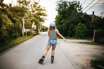 Woman roller skating on city street with helmet on summer from behind
