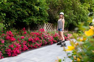 Woman roller skating in city park between flowers garden with helmet