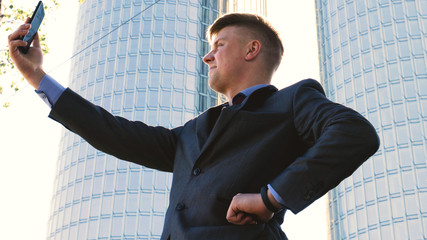 A successful handsome businessman in a suit, holding a mobile phone in his hand, making a selfie, a background of skyscrapers. Concept: communication, contacts, internet, chat, network.