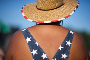 A man wears patriotic overalls and a straw hat on the third day of the Firefly Music Festival in Dover, Delaware