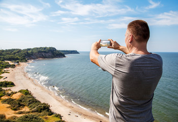 man in a gray t-shirt photographing seascape
