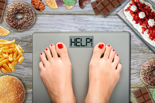 Junk food or sugar sweets temptations when you diet concept with woman feet on weight scale