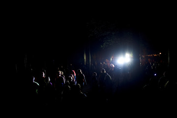 Revelers are illuminated as they walk though emergency lights at the Firefly Music Festival in Dover, Delaware