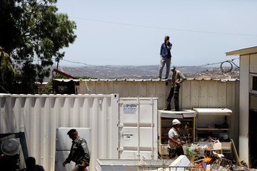 Jewish settlers stand on a roof of a structure during the eviction of buildings that an Israeli court deemed to have been built illegally in Tapuach West settlement, in the Israeli occupied West Bank