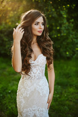 Beautiful and fashionable brunette model girl with bright makeup and sexy body in white stylish lace dress adjusting her hairstyle stands at the park an posing at the sunset