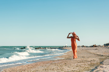Woman in orange dress on sea beach