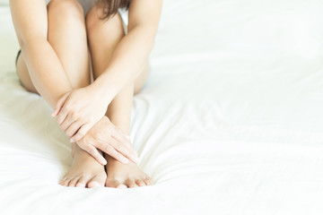 Closeup depresses woman sitting on white bed for health care and medical concept, selective focus
