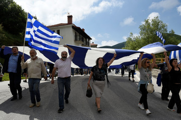 Protesters carry a giant Greek national flag during a demonstration against the agreement reached by Greece and Macedonia to resolve a dispute over the former Yugoslav republic's name, in Pisoderi village
