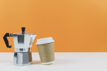 Coffee espresso maker with a paper coffee cup on a white table and orange wall background.Template mock up for adding your design.