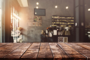 Empty old wood table top and blurred bokeh cafe and coffee shop interior background with vintage...