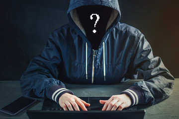 Anonymous hacker uses a laptop to hack the system. Stealing personal data. Creation and infection of malicious virus.