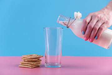 Woman's hand pours fresh milk from bottle into a glass and cookies on a pastel background. Healthy dairy products