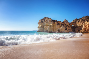 Wall Mural - Algarve, Portugal, a stunning sea ocean landscape with yellow rocks and azure water. The beauty of nature and the power of the ocean