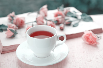 A cup of tea with pink flowers and open book