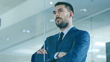Handsome Suited Businessman Looks out of the Office Window. Successful Man on the Top of the World.