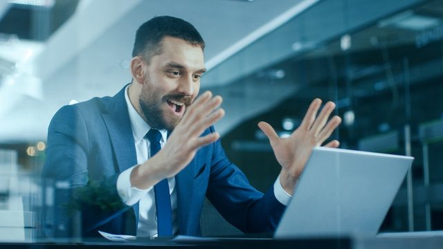 Handsome Businessman Works on a Laptop at His Desk, He Finished Job, Broke the Jackpot, Won Big and Is Happy and Celebrates His Success. Stylish Man in Modern Glass Office.