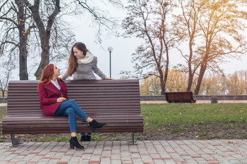 Female teenagers at the bench in an autumn city park