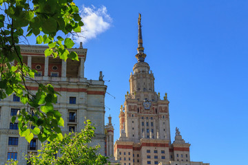 Towers of Lomonosov Moscow State University (MSU) against green trees and blue sky