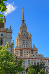 Buildings of Lomonosov Moscow State University (MSU) on a blue sky and green trees background