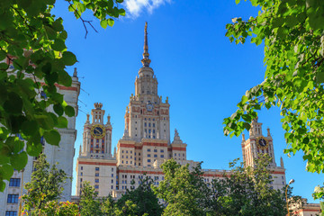 Buildings of Lomonosov Moscow State University (MSU) against green trees and blue sky in sunny summer evening