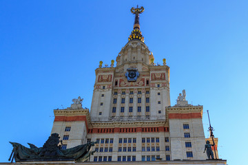 Tower above entrance to main building of Lomonosov Moscow State University (MSU) on a blue sky background
