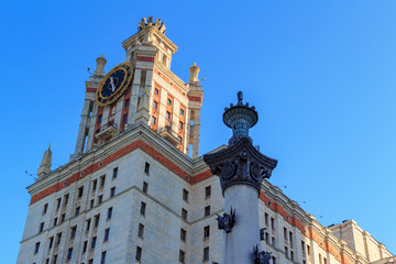 Tower with clock of Lomonosov Moscow State University (MSU) against column in sunny summer evening