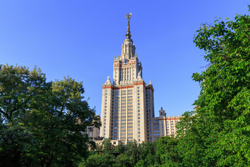 Lomonosov Moscow State University (MSU) in sunny summer evening against green trees