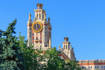 Tower with clock of Lomonosov Moscow State University (MSU) against green trees in sunny summer evening