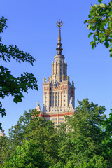 Moscow State University (MSU) against blue sky and green trees in sunny summer evening