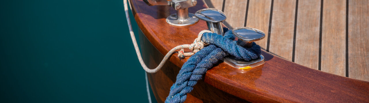 dock cleat on the side of a boat in a small marina, an element of yachting equipment