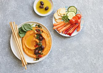 Hummus. Sweet potato, pumpkin or carrot Hummus served with fresh vegetables, seasoned with olives, herbs, extra virgin olive oil and paprika. Overhead view, copy space