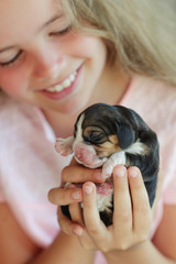 A child is holding a puppy