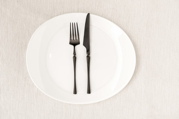 """Black fork and knife with a white plate on a linen tablecloth. Restorant signal with fork and knife meaning """"I have finished """""""