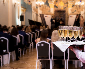 waiter offers champagne to guests at the event