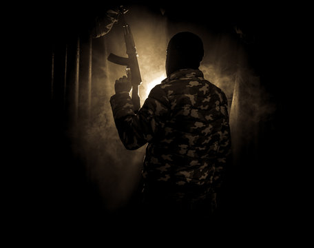 Silhouette of man with assault rifle ready to attack on dark toned foggy background or dangerous bandit in black wearing balaclava and holding gun in hand.