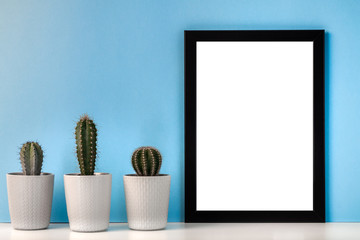 Black empty frame mockup on a blue background with three cactuses in a row