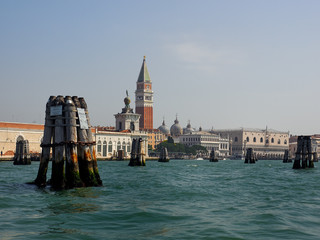 Wooden poles marking the channel in the lagoon in St Marks Basin, Venice, Italy with the Campanile and Doges Palace behind