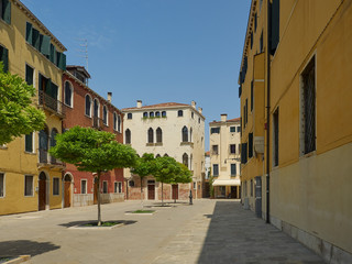 Square with green trees in Dorsoduro, Venice, Italy surrounded by historic colorful houses and apartments on a sunny day