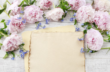 Vintage sheet of paper and pink peonies in the background