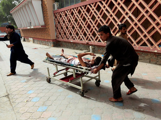 An injured man is pushed on a stretcher to a hospital after a car bomb in Jalalabad city