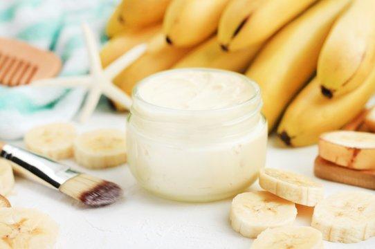 Homemade banana skincare beauty treatment mask. Jar of aromatic body butter,  fresh ripe yellow fruit, preparing yummy skin product. Soft focus.