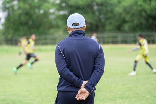 Football or socker coach observing kid football match.Healthy sport concept.